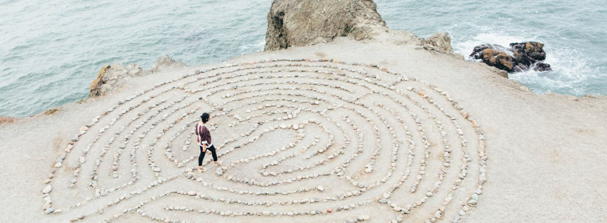 Woman walks a labyrinth made of rocks set on a beachy coastline with ocean water lapping against the shore around her