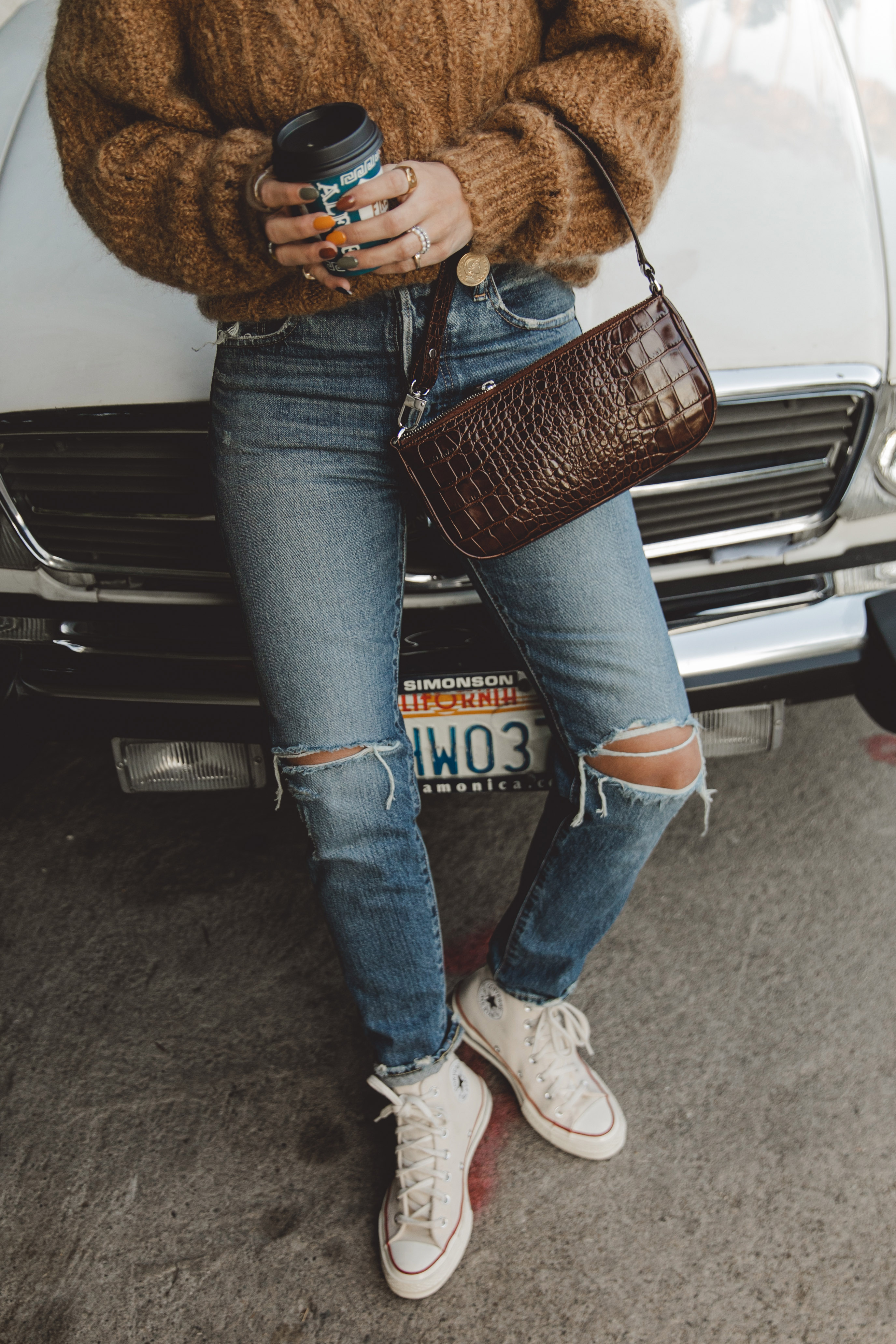 Sara is wearing Isabel Marant camel knit sweater, Moussy Vintage tapered jeans, By Far leather bag and All-Star retro sneakers