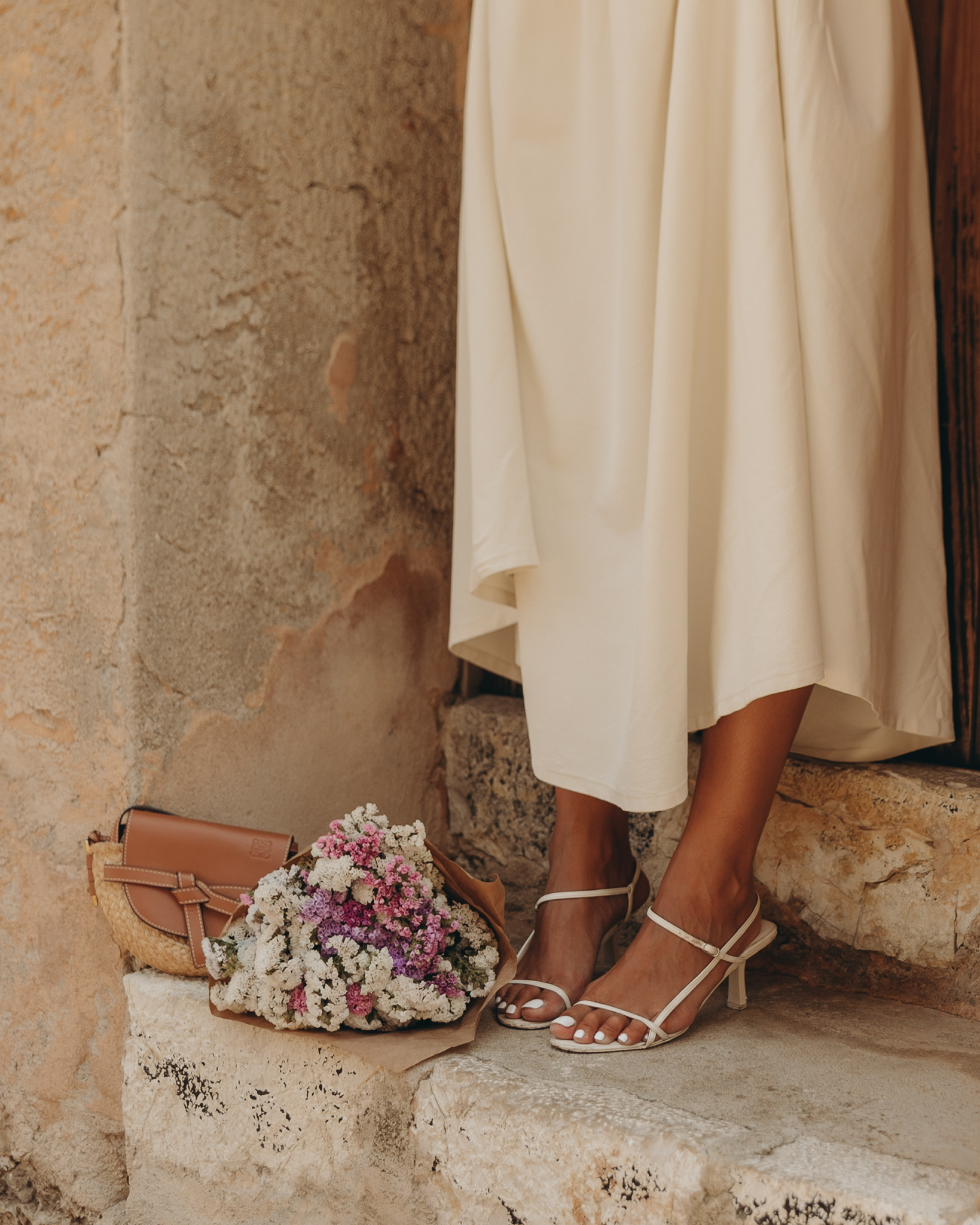 Sara from Collage Vintage is wearing a Cettire total look, Khaite Ren Ruched Midi Dress, Reike Nen Sandals, Loewe Gate Bag
