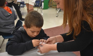 Elizabeth Williams helps a Greenland student make the pattern of a constellation in the bottom of a cup.