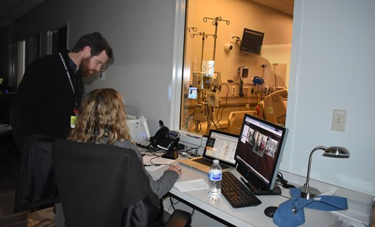 UAMS assistant professors Christopher Walter and Jennifer Vincenzo interact with the students from a control area of the sim labs.