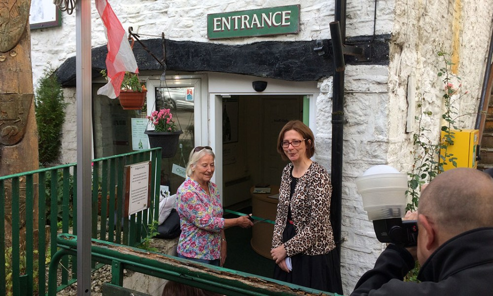 A local resident cutting the ribbon at a celebration of the new door (Bridgend Community Centre)