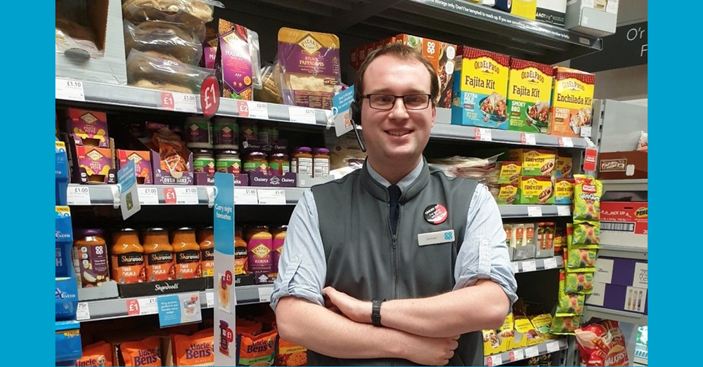 Store Manager James Owen stood in front of shelves of products