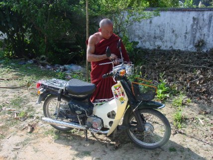 Kowita fixing his moped. Many of the monks were heavily tattooed.