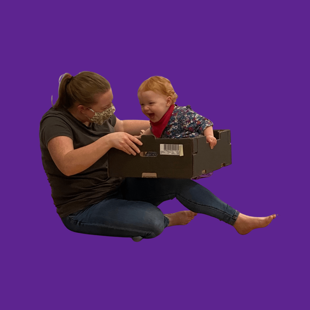 parent and toddler dancing with a box