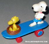 Woodstock sitting in nest and Snoopy standing wearing shorts on blue curved skateboard