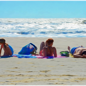 Family on blankets sunning themselves by the ocean