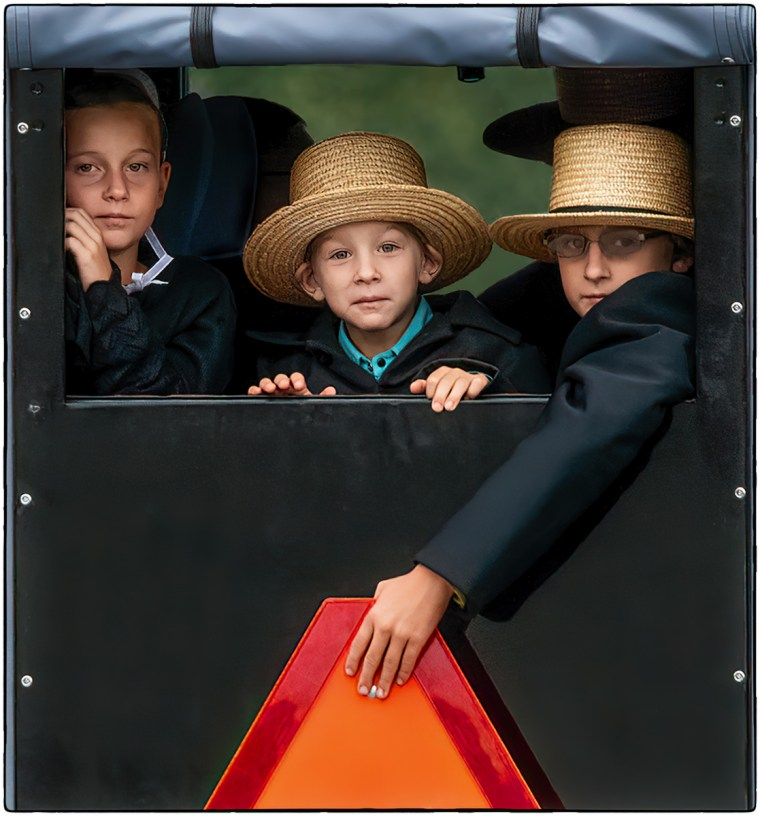 Three Amish children in Lancaster, Pennsylvania looking out the back window of their family's buggy going to Sunday services