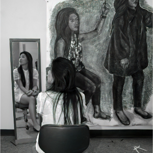 Girl artist sits before mirror with self-portrait life-size drawing