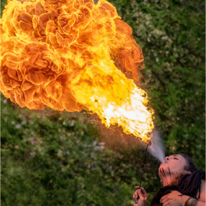 Girl fire eater blowing out large flames at Renaissance Fair