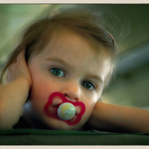 Little girl with red pacifier turning around in her seat on a train