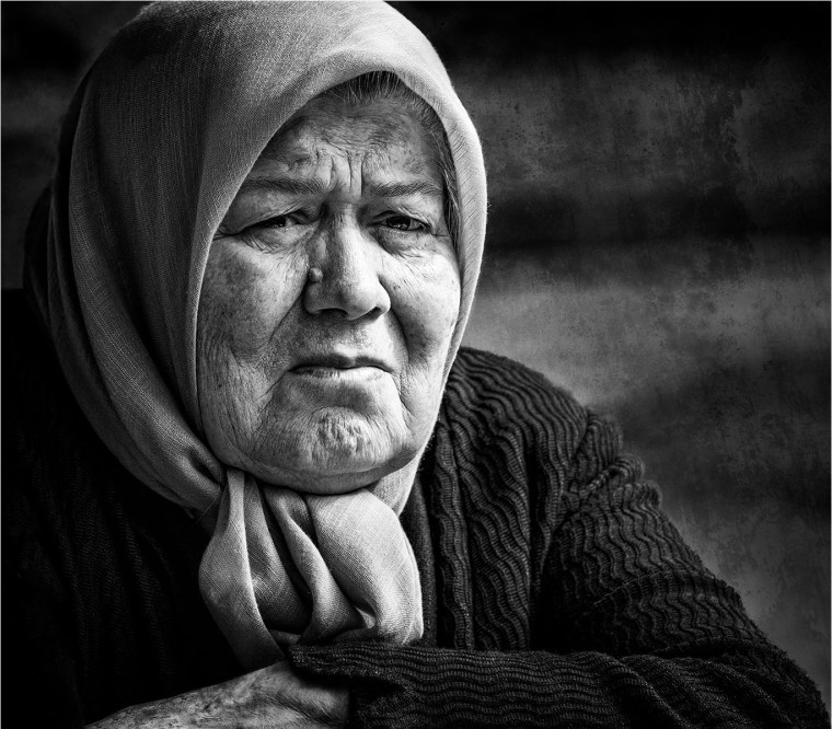 Older woman with old-fashioned scarf staring pensively into the distance