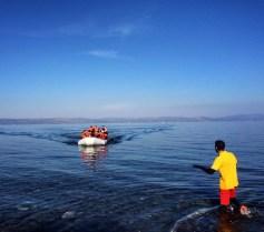 A Greek lifeguard attempts to calm refugees in an arriving raft. December 2015.