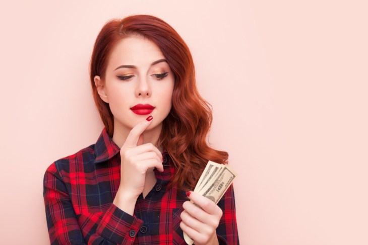 Woman looking at money in hand