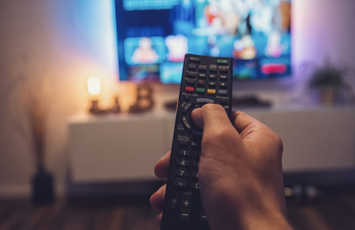 Person changing channels on TV with a remote