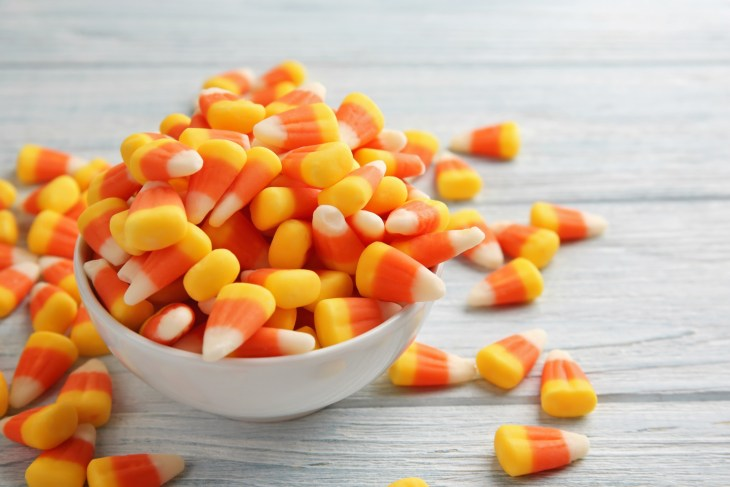 A mound of candy corn in a small white bowl