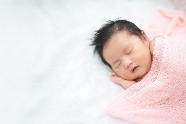 Baby Asian girl laying on a bed with a pink blanket over top