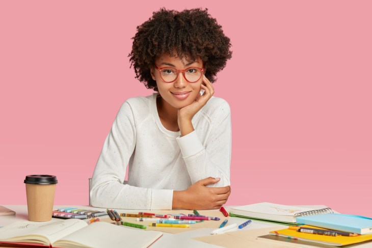 cartoonist in glasses has a notebook and colored pencils and crayons