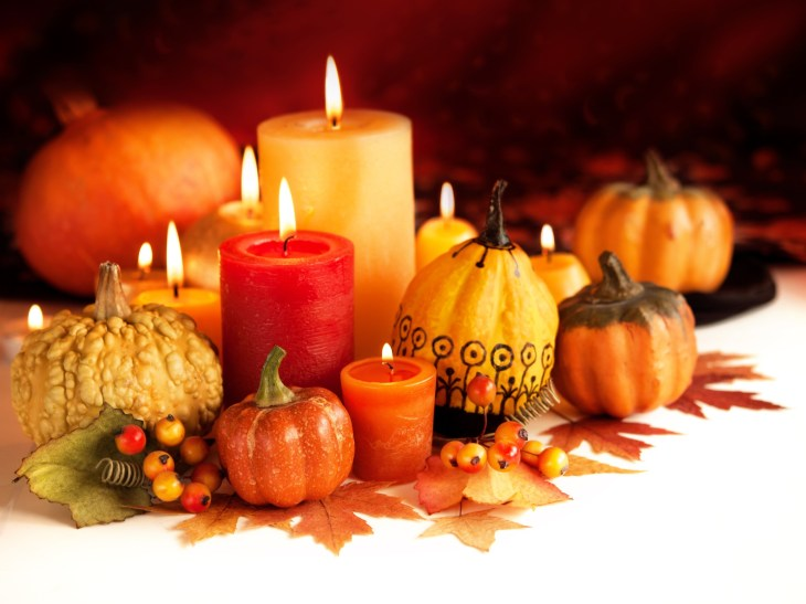 fall colored candles surrounded by pumpkins and gourds