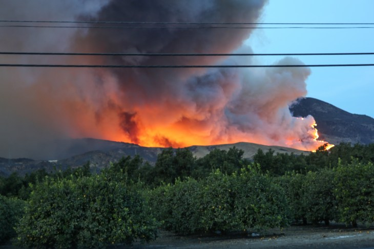 A wildfire burning in the valley with smoke billowing into the air