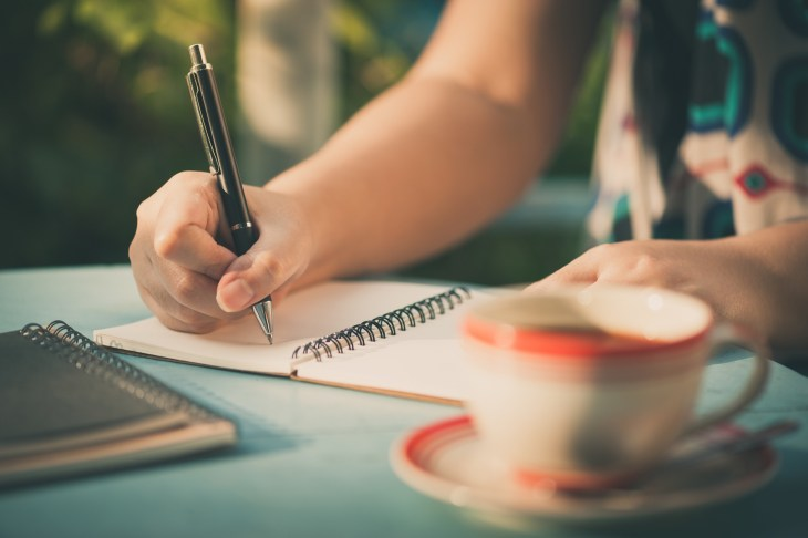 person writing in a journal at a coffee shop