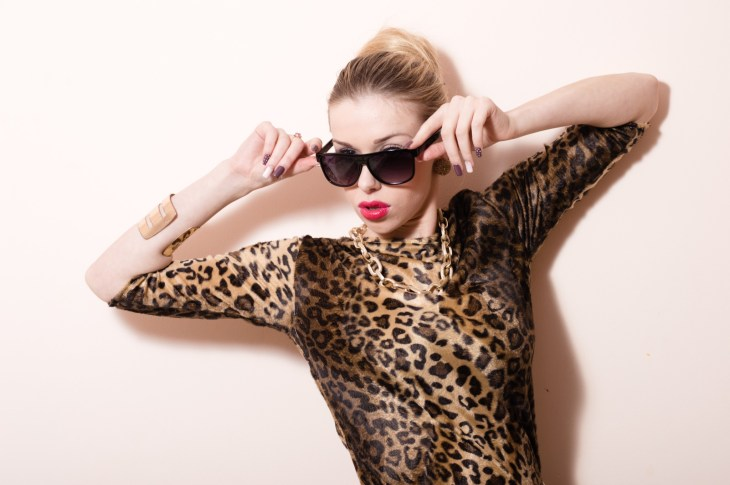 girl posing in cheetah print shirt with sunglasses on against light pink background
