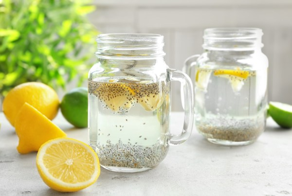glass of water filled with chia seeds and lemon slices with sliced lemons surrounding it