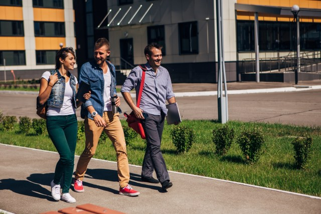 Group of friends smiling and walking on a college campus