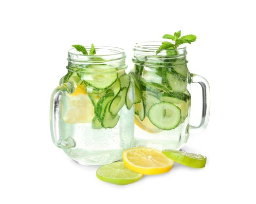 glass of water with cucumber, lemon, and mint on white background