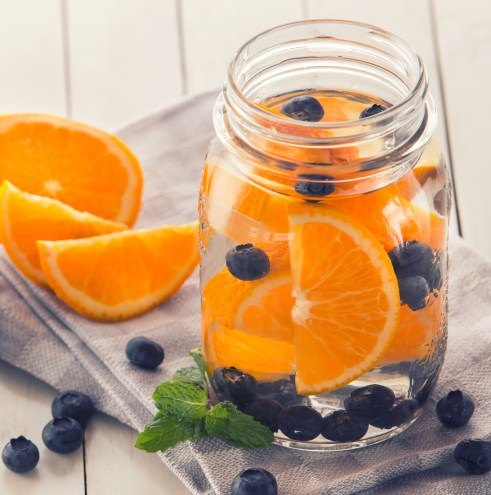 Mason jar of water infused with orange slices and blueberries