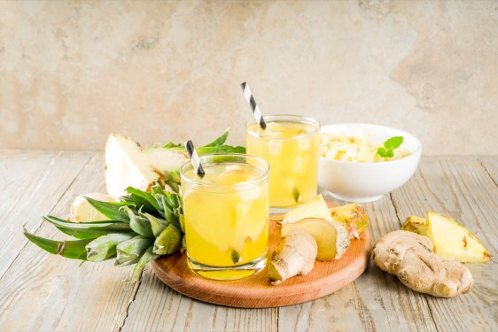 Glass of water with pineapple and ginger on a table with pineapple pieces surrounding it