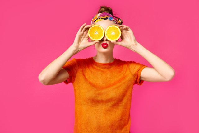 A woman in front of a pink background holding two oranges in front of her eyes