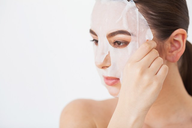 Lady putting on a sheet face mask