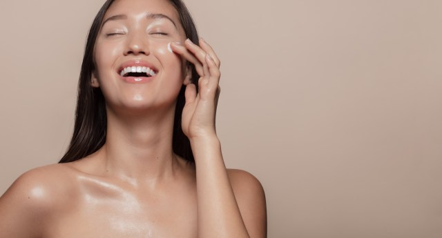 Young woman with highly moisturized skin smiling and applying cream to her face