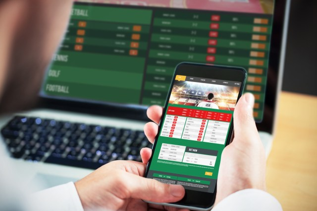 iPhone being used for betting next to laptop