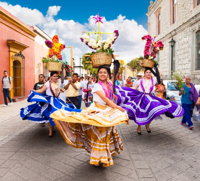 Ladies in colorful skirts dancing through the streets of Oaxaca, Mexico