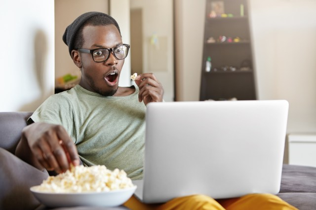 A man watching a show on his laptop while eating popcorn