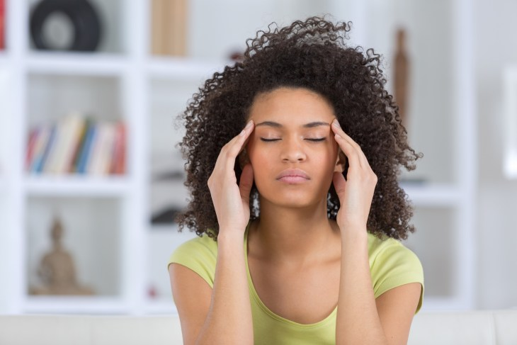 A woman with anxiety holding her head