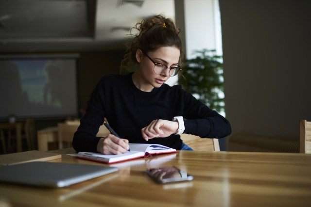 A young woman writing in her book while looking at her watch