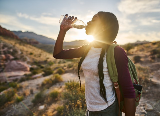 A woman drinking water while on a hike