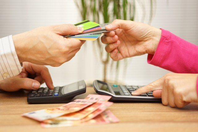 Two hands swapping credit cards and doing finances