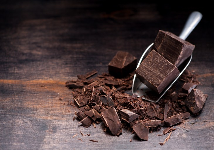 pieces of dark chocolate and shavings on a rustic wooden table