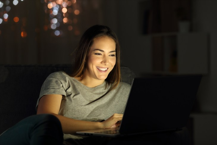 Happy lady using a laptop in the night sitting on a couch in the living room at home