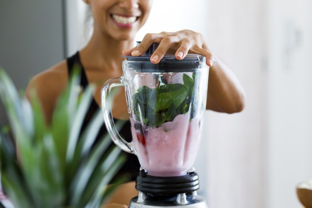 Young woman blending up fruits and vegetables for a delicious smoothie