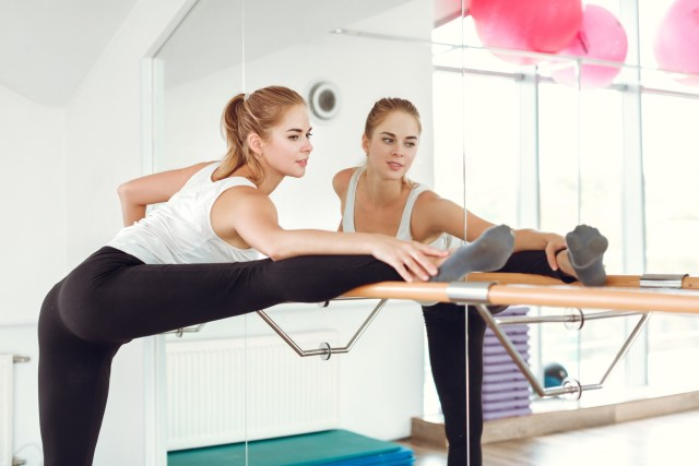 girl in leggings and tank top in a ballet studio leaning over stretching bar