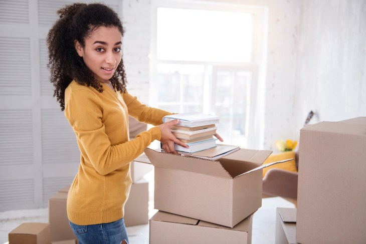 New start. Pleasant young girl taking a pile of books out of the box and posing for the camera while moving in to a new apartment