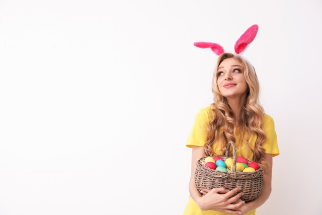 Young blonde woman with festive bunny ears cradling a basket of colorful Easter eggs