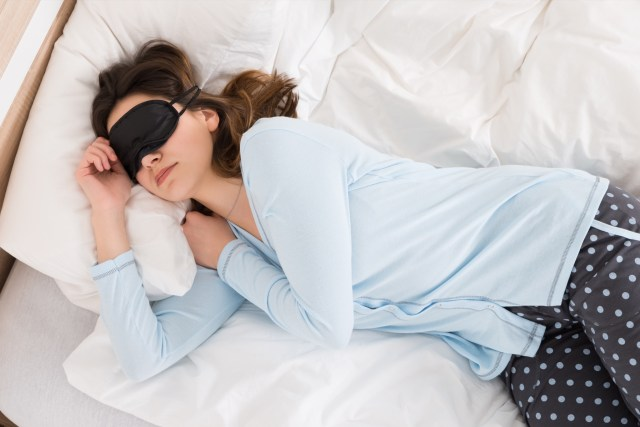 Young Woman Wearing Eyemask While Sleeping On Bed