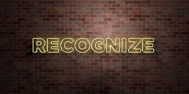 Yellow neon sign against brick wall that says 'recognize'