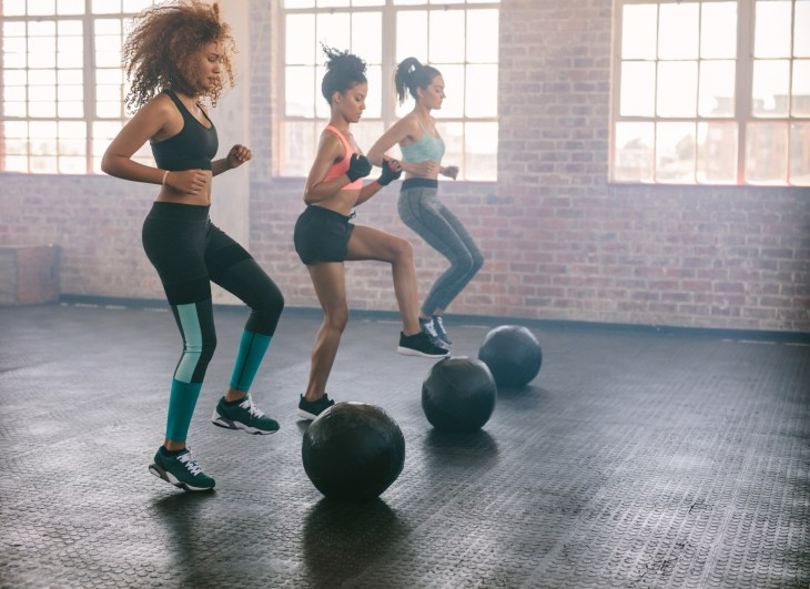 Three women in an studio working out with a medicine ball doing toe taps
